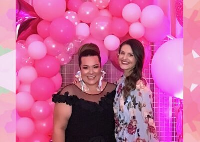 two guests at the longest table photo in front backdrop of balloons